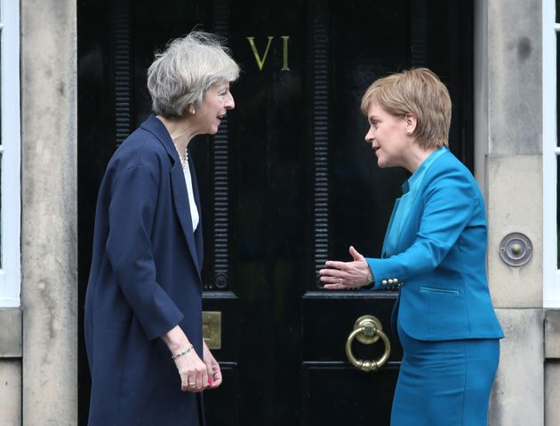 Theresa May (left) is greeted by Scotland's First Minister Nicola Sturgeon at Bute House in