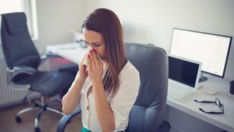 Young businesswoman blowing her nose, sits at her desk