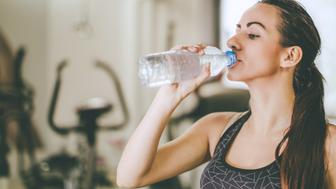 sporty woman drinking water from bottle