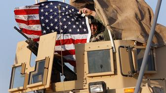 A U.S. Army soldier waves an American flag after crossing into Kuwait during the last convoy out of Iraq December 18, 2011. The last convoy of U.S. soldiers pulled out of Iraq on Sunday, ending nearly nine years of war that cost almost 4,500 American and tens of thousands of Iraqi lives and left a country still grappling with political uncertainty. .   REUTERS/Shannon Stapleton   (KUWAIT - Tags: MILITARY CONFLICT POLITICS)
