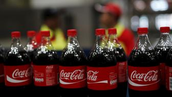 Workers stand near bottles of Coca-Cola on a newly inaugurated production line at the Cikedokan Plant in Bekasi, West Java near Jakarta March 31, 2015. The Coca-Cola company inaugurated two new production lines as part of an investment package worth some $500 million to accelerate growth in the Indonesian market.  REUTERS/Darren Whiteside