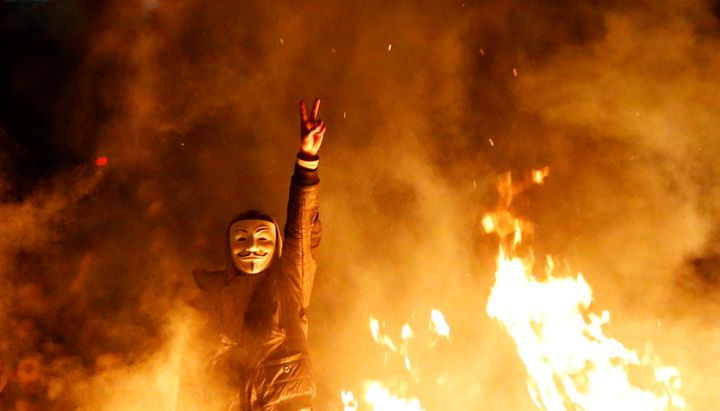 An anti-government protester wearing a Guy Fawkes mask gestures behind a barricade that they set on fire during a demonstrati