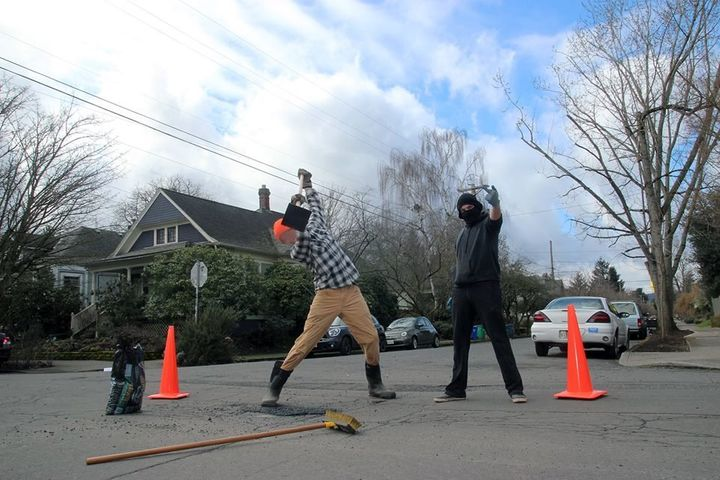 Safety first! Anarchists in Portland make sure to put out orange cones while they fix potholes around the city.