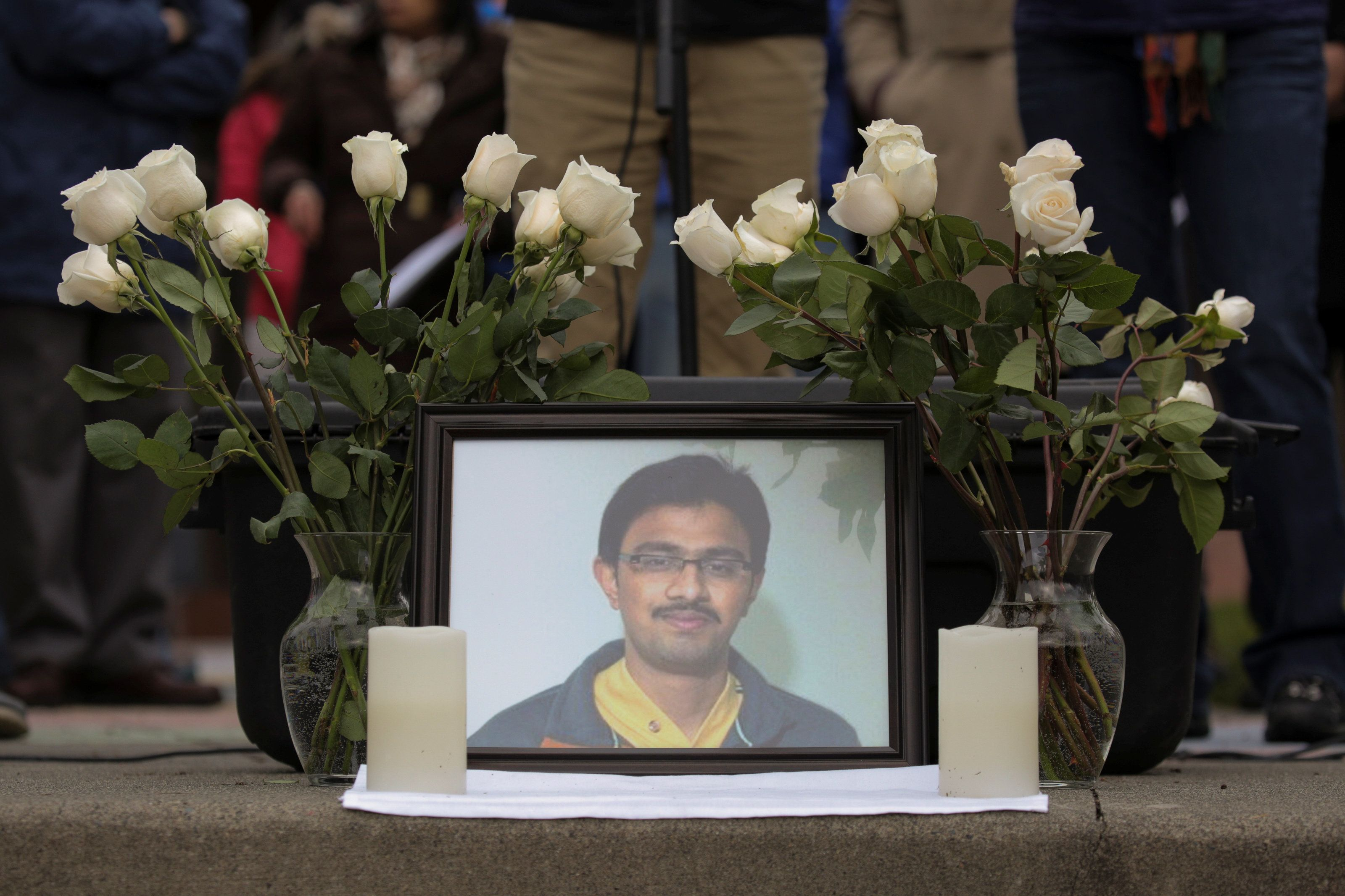 A picture of Srinivas Kuchibhotla, an immigrant from India who was recently shot and killed in Kansas, is surrounded by roses