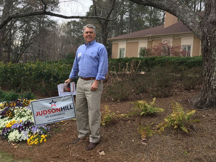 Former Georgia state Sen. Judson Hill (R) poses with a yard sign as he campaigns for the congressional seat vacated by Presid