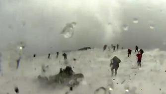 People are seen running from Italys Mount Etna volcano following several unexpected explosions on Thursday