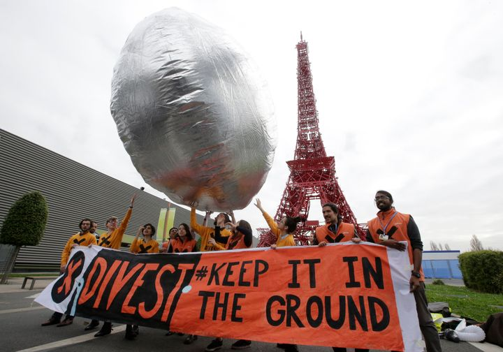 Divestment is now a global movement. Here, protesters in France in December 2015 call for investment funds to move their mone