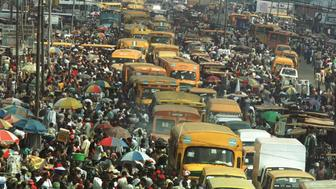 Commuters and traders of the Oshodi area of Lagos, the commercial nerve centre of Nigeria with a population of over twelve million people, make their way through crowded streets on April 30, 2001. The Nigeria umbrella workers union-Nigeria Labour Congress marks international workers day on May 1.  CLH/