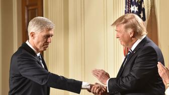 Judge Neil Gorsuch (L) shakes hands with US President Donald Trump after he was nominated for the Supreme Court, at the White House in Washington, DC, on January 31, 2017. President Donald Trump nominated federal appellate judge Neil Gorsuch as his Supreme Court nominee, tilting the balance of the court back in the conservatives' favor. / AFP / Nicholas Kamm        (Photo credit should read NICHOLAS KAMM/AFP/Getty Images)