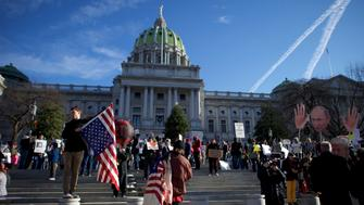 HARRISBURG, PA - DECEMBER 19:   Donald Trump protestors demonstrate outside the Pennsylvania Capitol Building before electors arrive to cast their votes from the election at December 19, 2016 in Harrisburg, Pennsylvania.  Electors from all 50 states cast votes today in their respective state capitols.  Donald J. Trump won Pennsylvania by less than 1%, the first Republican to carry the state since George H. W. Bush 1992.  (Photo by Mark Makela/Getty Images)
