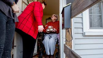 WESTBROOK, ME - DECEMBER 25: Nancy Brennerman, (cq) center, chats with Josephine Hayward,  (cq) 93, of Portland, after delivering a meal to Hayward as part of the Southern Maine Agency on Aging's Meals on Wheels program Christmas Day, Friday, December 25, 2015. City Councillor David Brennerman (cq)  started volunteering with the program in 1976 and on Friday was delivering meals with Nancy, (cq) his wife, and their daughter Molly. (cq) This year's meal included ham with a raisin sauce, sweet potatoes, a broccoli casserole, bread, and apple pie for dessert. (Photo by Gabe Souza/Portland Press Herald via Getty Images)