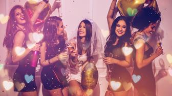 Young girlfriends celebrating bride night. Bride is wearing a veil and a T-shirt with the inscription ''BRIDE'', bridesmaids are wearing T-shirts with the inscription ''Squad''.  Standing in front of a white wall, cheering with champagne and dancing. Room is decorated with star and heart shaped balloons.
