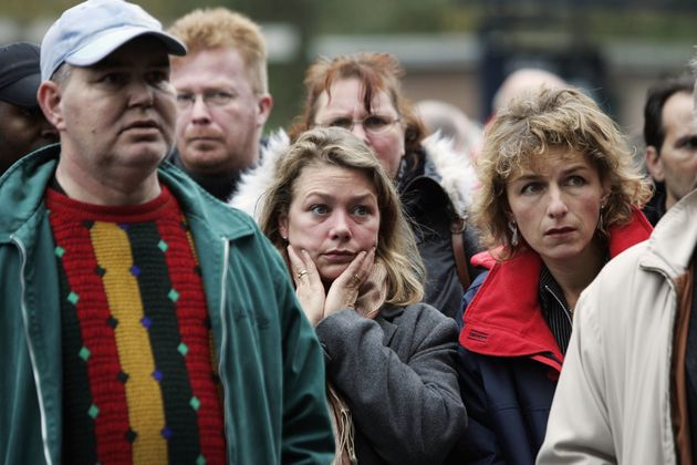 People watch a TV broadcast near to the crime scene where Dutch filmmaker Theo van Gogh was killed in...