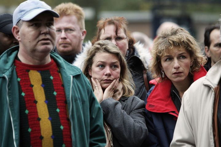 People watch a TV broadcast near to the crime scene where Dutch filmmaker Theo van Gogh was killed in Amsterdam. Nov. 2, 2004