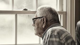 A senior man wearing a hearing aid is sitting staring through the mesh screen and hazy, speckled, unwashed windows. Intentionally grainy, grungy image. Desaturated and sepia toned.
