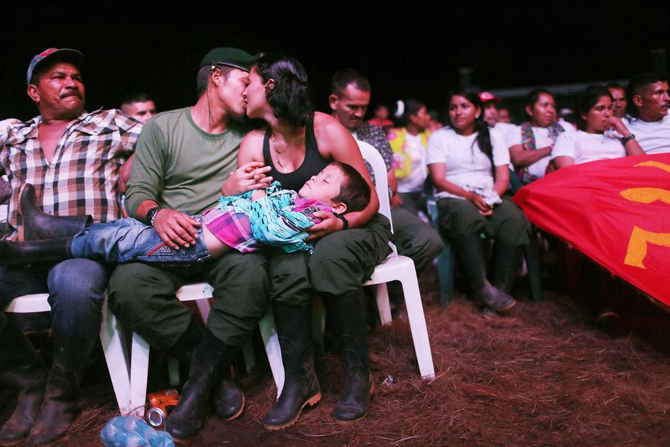 FARC guerrillas Willington and Veronica kiss while holding their nephew at the 10th FARC conference, in the Yari Plains.&nbsp