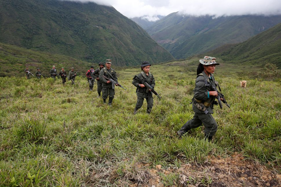 Members of the 51st Front of the FARC patrol in the remote mountains of Colombia. Aug. 16.