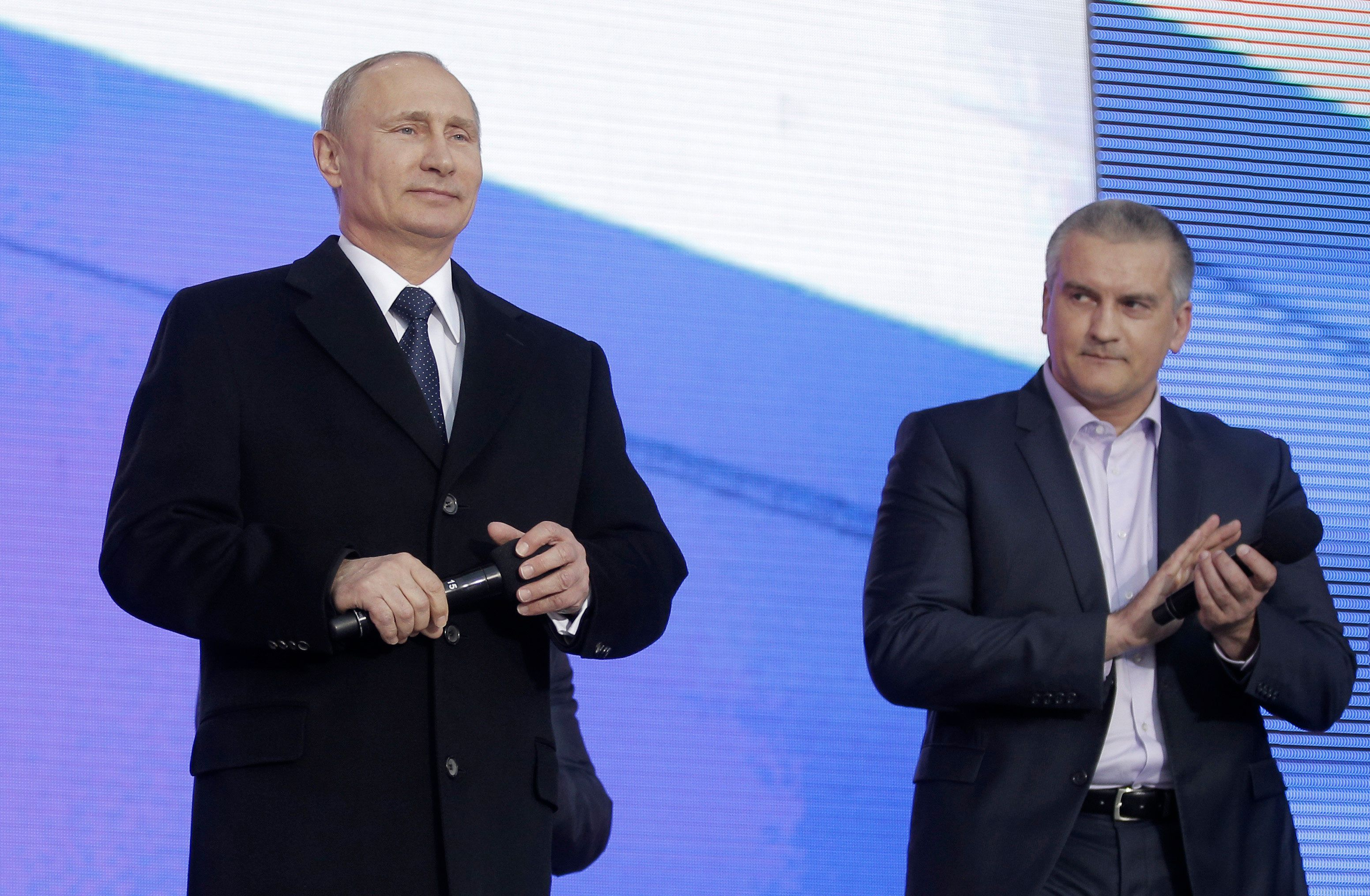 Russian President Vladimir Putin (L) and Crimean Prime Minister Sergei Aksyonov attend a festive concert marking the first anniversary of the Crimean treaty signing in central Moscow, March 18, 2015. Putin said on Wednesday his country, hit by Western economic sanctions over the Ukraine crisis, would overcome all difficulties from outside. REUTERS/Maxim Shipenkov/Pool (RUSSIA - Tags: ANNIVERSARY POLITICS)