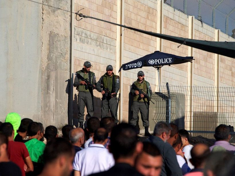 Israeli Border Police officers stand guard as Palestinians wait to cross through the Qalandiyah checkpoint, June 2016. Mohama