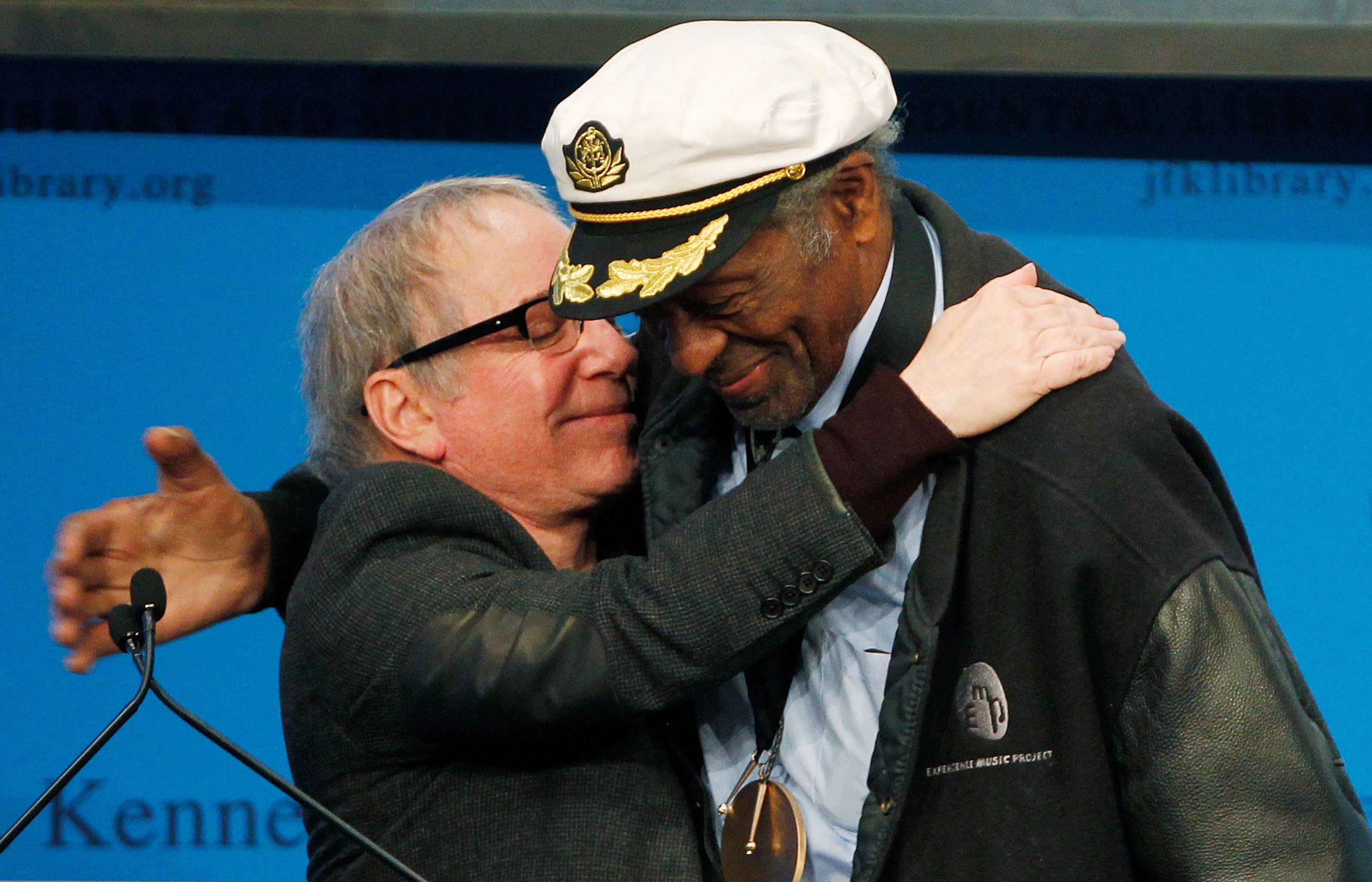 Musician Paul Simon (L) hugs Chuck Berry after presenting him with the 2012 Awards for Song Lyrics of Literary Excellence at the John F. S- Kennedy Presidential Library and Museum in Boston, Massachusetts February 26, 2012. REUTERS/Jessica Rinaldi (UNITED STATES - Tags: ENTERTAINMENT)