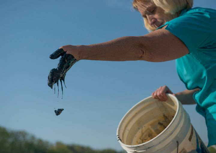 Diana Muller, the former director of scientific research at the South River Federation flicks 'black muck' from her hands aft