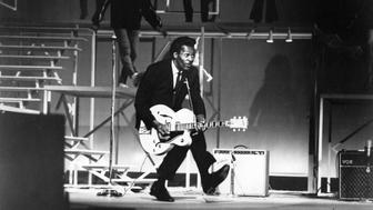 SANTA MONICA, CA - DECEMBER 29: Rock and roll guitarist Chuck Berry performs his 'duck walk' as he plays his electric hollowbody guitar at the TAMI Show on December 29, 1964 at the Santa Monica Civic Auditorium in Santa Monica, California. Other performers included James Browm, The Rolling Stones, The Beatles and Jan & Dean. (Photo by Michael Ochs Archives/Getty Images)