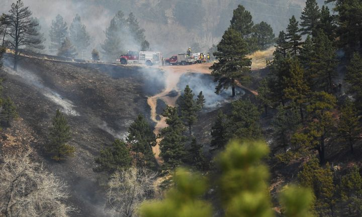 Fire crews work at extinguishing the wildfire in Sunshine Canyon.