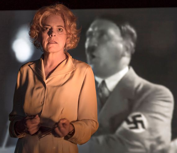 Stacy Ross as Leni Riefenstahl, defending herself; behind her, an image from <em>Triumph of the Will</em>