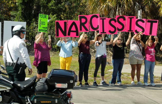 Anti-Trump protesters hold up signs as the motorcade of US President Donald Trump passes by in West Palm...