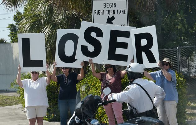 Protestors are seen as the motorcade of US President Donald Trump passes by en route to Palm Beach International...