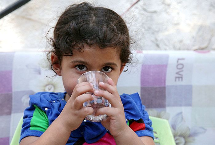 Mayar drinks clean water at home after the installation of a water network at her home in Gaza.