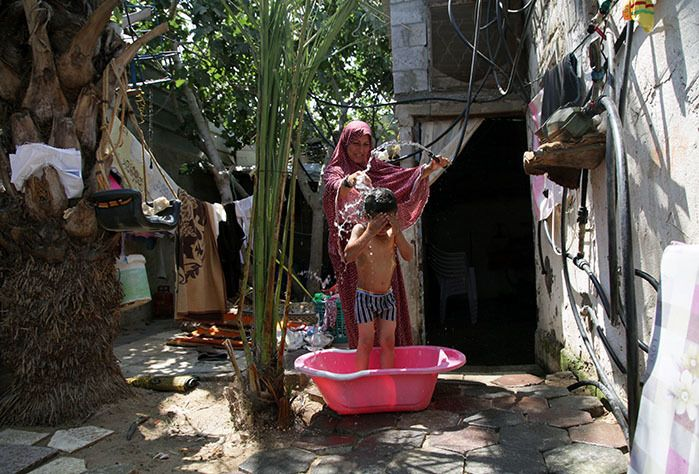 Gaza mother Rawda bathes her children using water from the new network installed in her village.