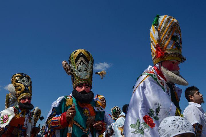 Costumed revelers dance through the streets of Philadelphia for the Carnaval de Puebla on April 27, 2014.