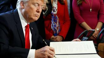 U.S. President Donald Trump signs an executive order rolling back regulations from the 2010 Dodd-Frank law on Wall Street reform at the White House in Washington, U.S. February 3, 2017.  REUTERS/Kevin Lamarque