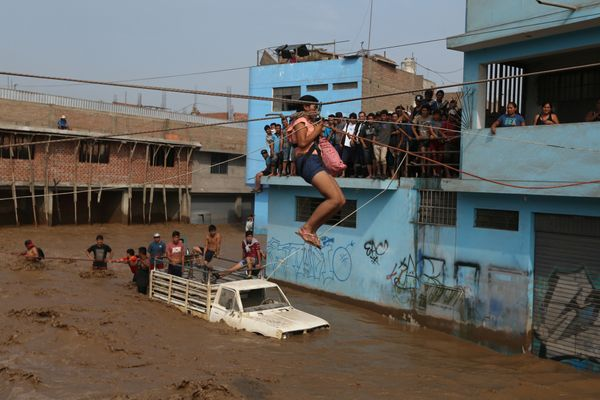 A woman gets rescued via zipline in Lima, the country's capital, which normally remains pretty dry.