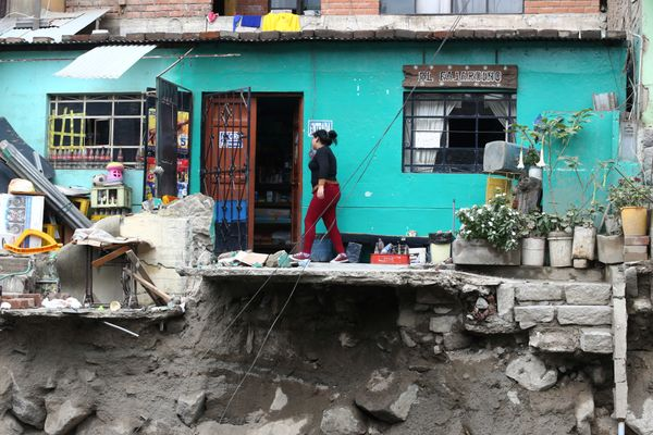 A woman walks outside her house after a landslide and flood in Chosica.