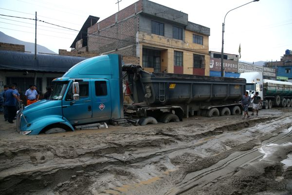 A truck submerged in mud is seen on the central highway.