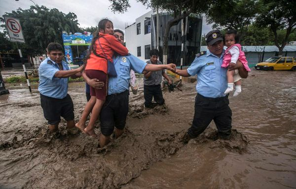 Municipality guards help residents cross a flooded street in Trujillo.