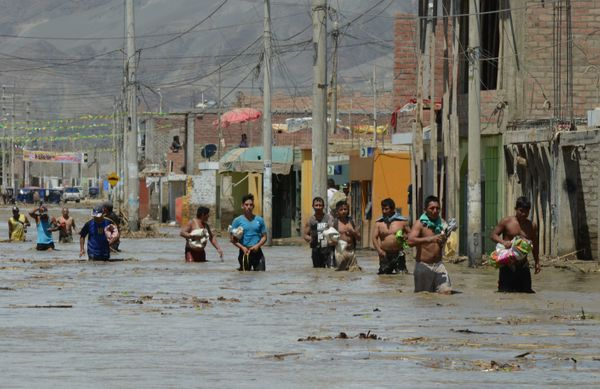 Local residents of the town of Huarmey, 300 kilometers north of Lima, wade through muddy water in the street.