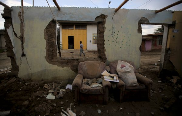A man walks next to a flooded home damaged after heavy rain in Castilla district of Piura.