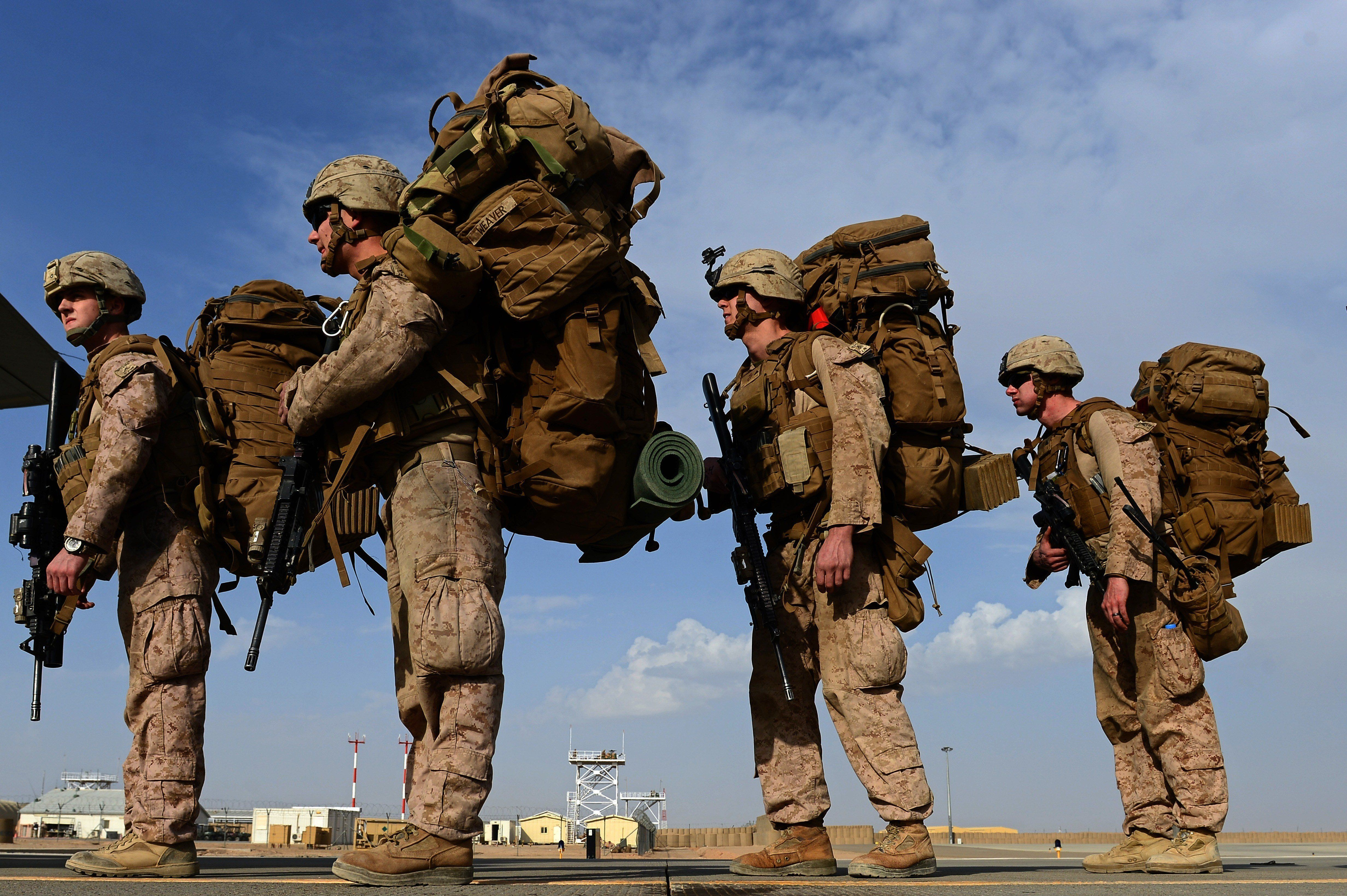 Marines individually carry heavy loads as they wait to board an aircraft in Afghanistan.