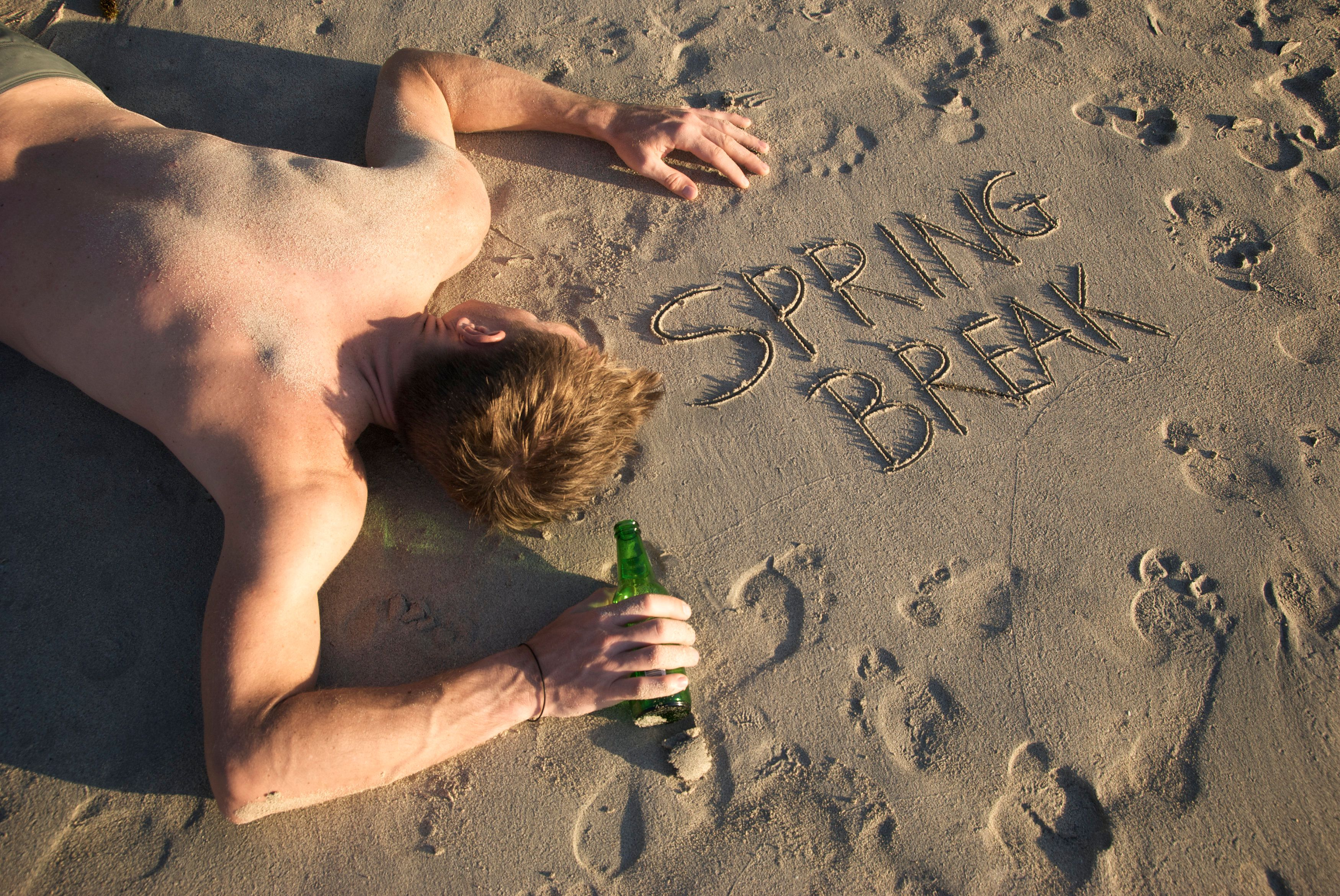 Shirtless guy passes out with beer bottle next to Spring Break message in footprint sand