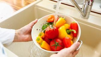 Housewife preparing vegetables for cooking in a domestic kitchen. She is washing paprika, tomatoes in a colander under running tap water. The water is splashing into the sink.
