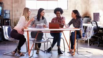 Group Of Female Designers Having Meeting In Modern Office