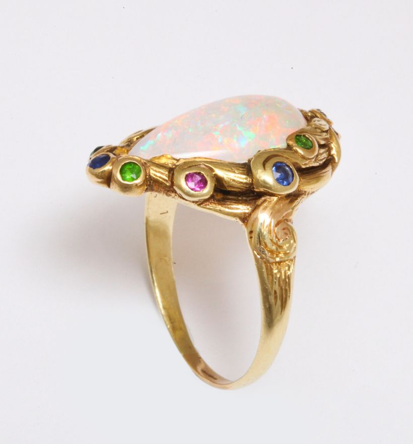 Pat Saling's Art Nouveau ring of center opal and acent colored stones in high karat gold, circa 1890.