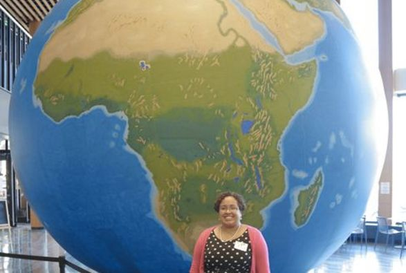 Natacha Scott, the social studies director for Boston Public Schools, stands before a massive globe that shows the