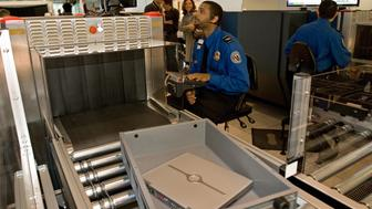 A Transportation Security Administration (TSA) officer reads the X-ray of a laptop computer that rides in a new style bin for carry-ons at the Checkpoint Evolution prototype at Baltimore-Washington International Airport's security screening checkpoint B in the Southwest terminal on April 28, 2008. The checkpoint is calm and quiet with officers wearing headsets to keep radio traffic down and new inspection machines and proceedures.                AFP PHOTO/Paul J. RICHARDS (Photo credit should read PAUL J. RICHARDS/AFP/Getty Images)