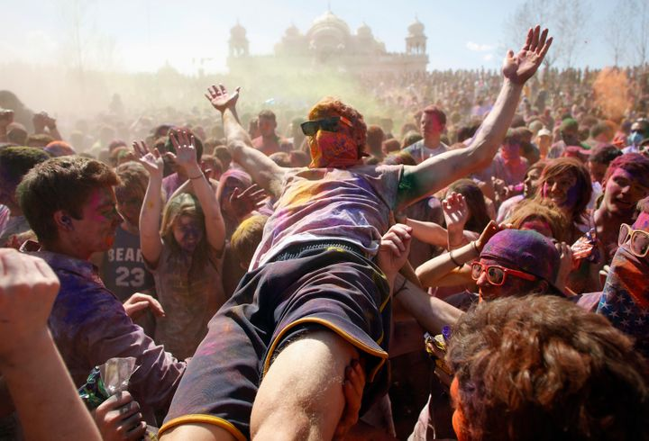 Participants crowd surf, dance and throw colored chalk during the Holi Festival of Colors at the Sri Sri Radha Krishna Temple