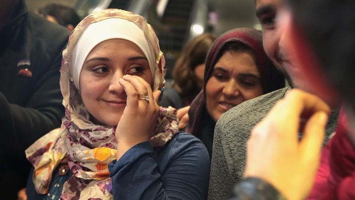 Syrian refugee Baraa Haj Khalaf wipes away a tear after arriving at O'Hare Airport with her family on a flight from Istanbul,
