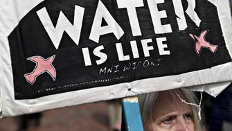 A demonstrator holds a 'Water Is Life' sign during a protest against the Dakota Access Pipeline (DAPL) in Washington, D.C., U.S., on Friday, March 10, 2017. The Standing Rock Sioux Tribe and Indigenous grassroots leaders arranged for the march to protect native sovereignty, keep fossil fuels in the ground and stop construction of the DAPL project. Photographer: Andrew Harrer/Bloomberg via Getty Images